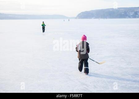 Sweden, Vastergotland, Lerum, Lake Aspen, Siblings (6-7, 8-9) playing ice hockey on lake - Stock Photo