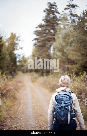 Sweden, Vastergotland, Lerum, Female backpacker walking away along earth road leading through forest - Stock Photo