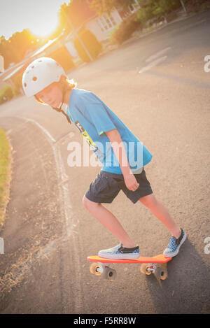 Sweden, Smaland, Anderstorp, Portrait of boy (10-11) riding red shortboard in street - Stock Photo