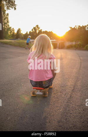 Sweden, Smaland, Anderstorp, Portrait of girl (8-9) sitting on red shortboard in street - Stock Photo