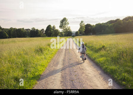 Sweden, Bohuslan, Halleback, Boy (10-11) cycling away along earth road leading through fields - Stock Photo