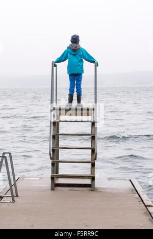 Sweden, Bohuslan, Halleback, Rear view of boy (10-11) standing on diving tower built on edge of pier - Stock Photo