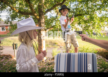 Sweden, Smaland, Anderstorp, Mom playing with her children (8-9, 10-11) in back yard - Stock Photo