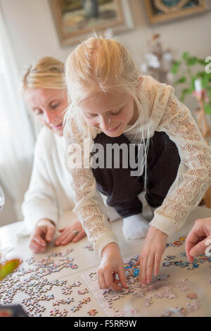 Sweden, Girl (8-9) making jigsaw puzzle - Stock Photo