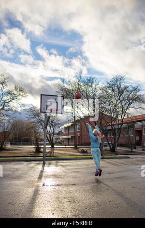 Sweden, Vastergotland, Lerum, Girl (10-11) playing basketball - Stock Photo