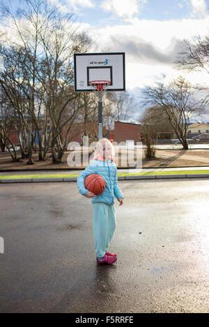Sweden, Vastergotland, Lerum, Portrait of girl (10-11) playing basketball - Stock Photo