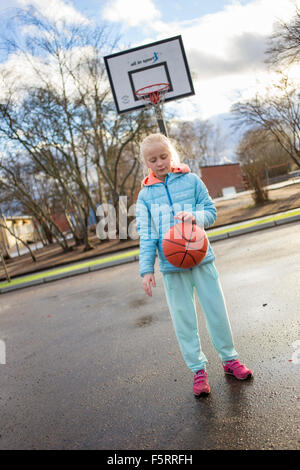 Sweden, Vastergotland, Lerum, Girl (10-11) playing basketball - Stock Photo