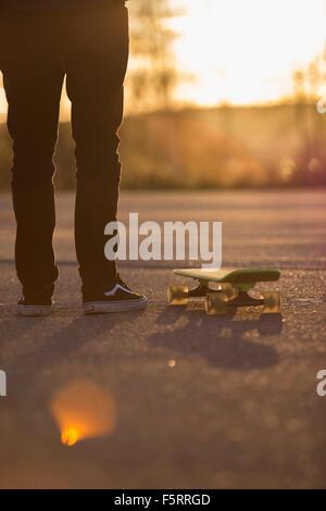 Sweden, Vastergotland, Lerum, Man with skateboard on road at sunset - Stock Photo
