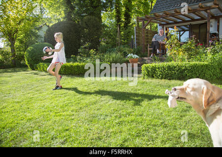 Germany, Lower Saxony, Girl (10-11) playing in front of house, man sitting on background - Stock Photo