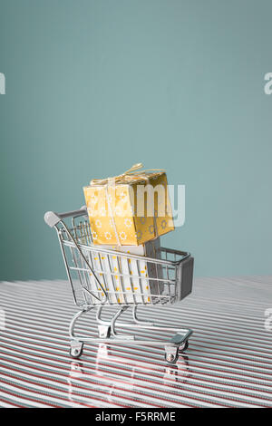 mini trolley with christmas present on xmas stripe against a blue background - Stock Photo