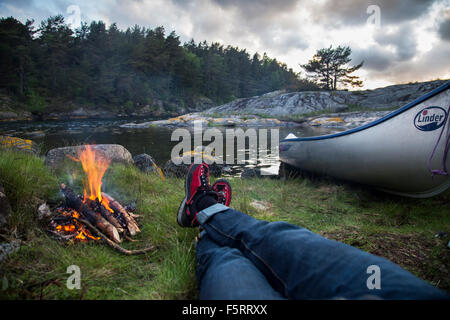Sweden, West Coast, Bohuslan, Flato, Personal perspective of man lying by campfire on riverbank - Stock Photo