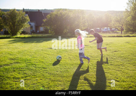 Sweden, Narke, Garphyttan, Girl (10-11) and boy (12-13) playing soccer in garden - Stock Photo