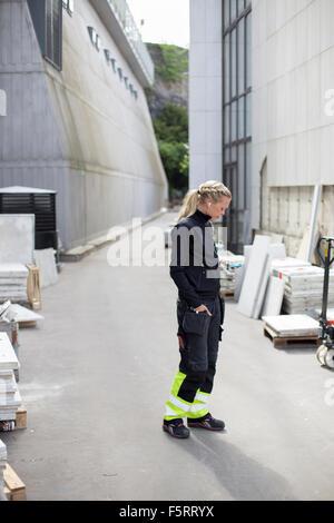 Sweden, Vastergotland, Woman - construction worker wearing headphones - Stock Photo