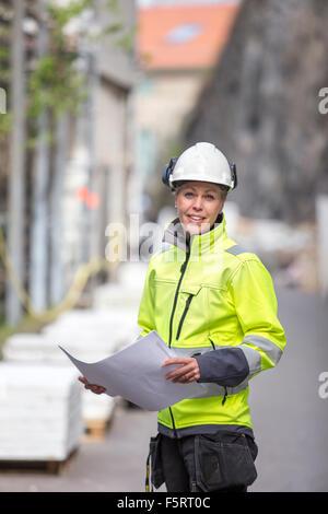 Sweden, Vastergotland, Smiley construction worker with blueprints - Stock Photo