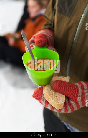 Close-up view of hands of woman wearing mittens holding bowl of soup and slice of bread - Stock Photo