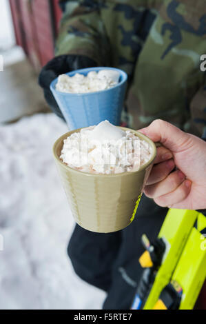 Sweden, Stockholm, Bjorkhagen, Hammarbybacken, Cropped view of man and woman holding mugs of hot chocolate with - Stock Photo