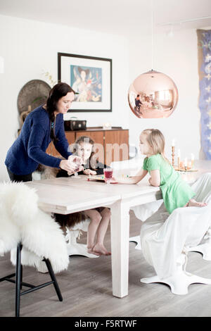 Sweden, Mom giving juice to her daughters (6-7) - Stock Photo