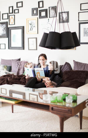 Sweden, Mom reading to her daughters (6-7) - Stock Photo