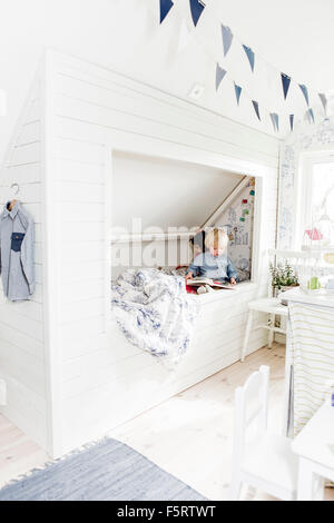 Sweden, Boy and girl (2-3) reading books in bedroom - Stock Photo