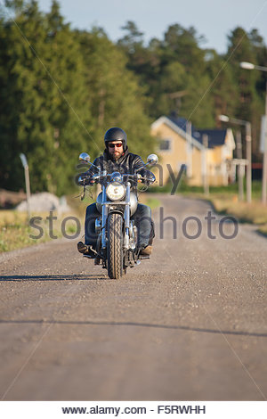 Sweden, Vasterbotten, Man riding on motorbike in summer - Stock Photo