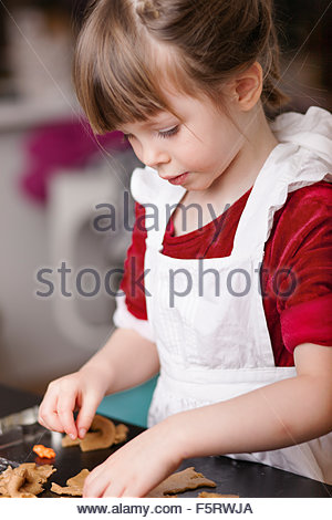 Sweden, Girl (4-5) making gingerbread cookies - Stock Photo