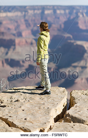 USA, Arizona, Grand Canyon, Woman standing on edge and looking at view - Stock Photo