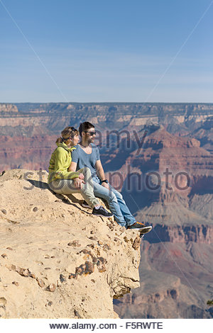USA, Arizona, Grand Canyon, Couple sitting on edge and looking at view - Stock Photo