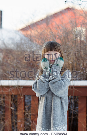 Sweden, Vasterbotten, Little girl (4-5) wearing sweater and mittens - Stock Photo