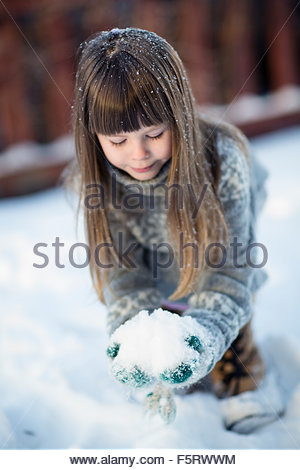 Sweden, Vasterbotten, Little girl (4-5) playing with snow - Stock Photo