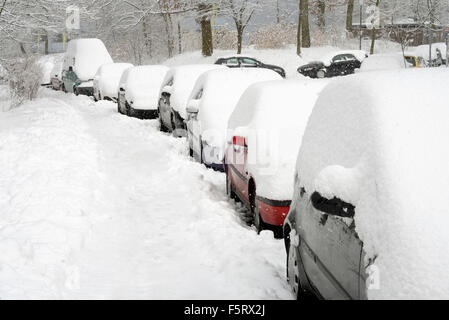 Winter scene containing a sidewalk and cars parking in a row on the street, all covered in snow - Stock Photo