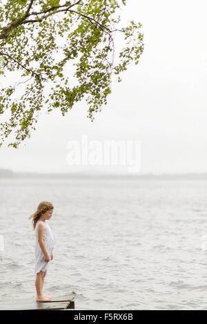 Sweden, Vastmanland, Bergslagen, Hallefors, Sangshyttan, Girl (4-5) standing on jetty by lake
