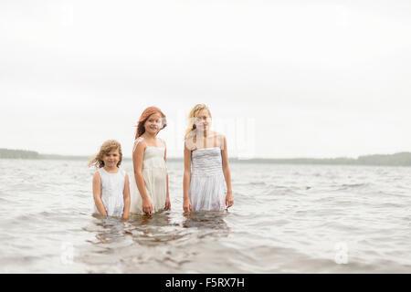 Sweden, Vastmanland, Bergslagen, Hallefors, Sangshyttan, Three girls (4-5, 8-9, 10-11) standing in water - Stock Photo