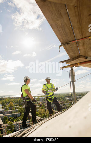 Sweden, Narke, Orebro, Construction workers on roof - Stock Photo