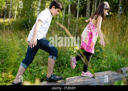 Sweden, Vastmanland, Bergslagen, Boy (10-11) and girl (6-7) walking along log - Stock Photo