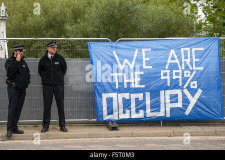 Police remove a vicar from a blockade during a protest against the DSEI, one of the world's largest arms fairs. - Stock Photo