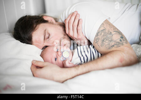 Sweden, Father and baby boy (0-1 months) resting - Stock Photo