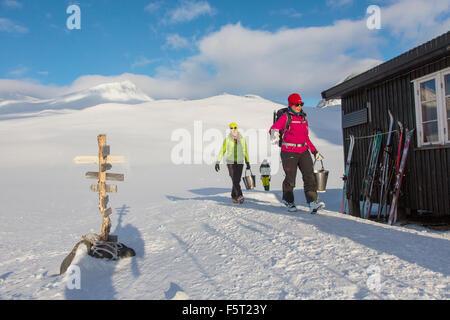Sweden, Lapland, Women carrying water buckets - Stock Photo