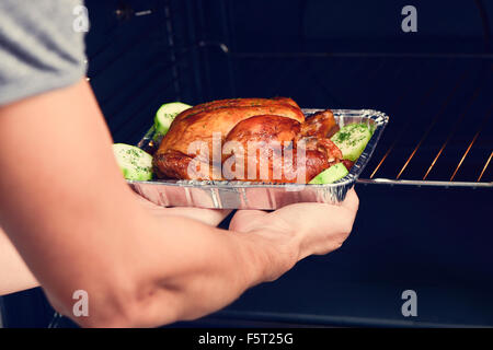 closeup of a young caucasian man preparing an appetizing roast turkey in the oven - Stock Photo