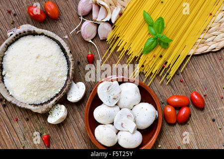 high-angle shot of a rustic wooden table with the ingredients to prepare a recipe of pasta, such as grated cheese, - Stock Photo