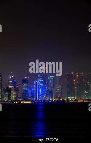 Qatar, Doha, Skyscrapers illuminated at night - Stock Photo