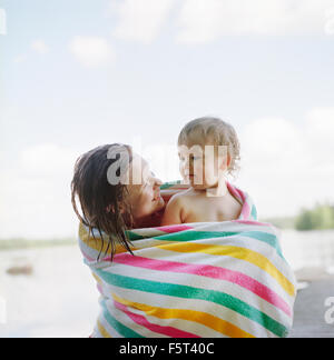 Finland, Uusimaa, Lapinjarvi, Mother and daughter (2-3) wrapped in towel - Stock Photo