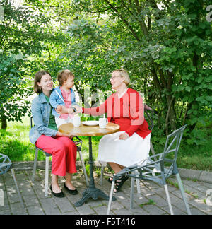 Finland, Helsinki, Uusimaa, Portrait of mother, grandmother and child (2-3) in sidewalk cafe - Stock Photo