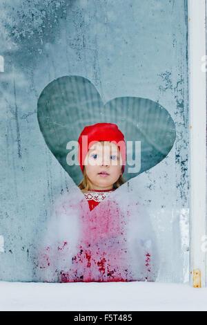 Portrait of girl (4-5) looking through frozen window - Stock Photo