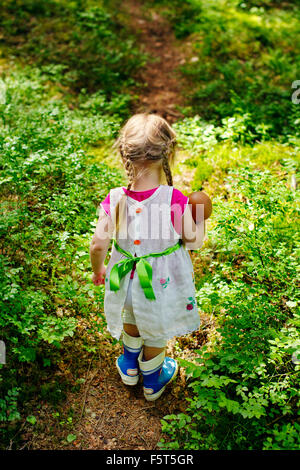 Finland, Paijat-Hame, Rear view of girl (2-3) with doll on footpath in forest - Stock Photo