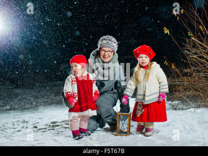 Finland, Portrait of grandmother with granddaughters (12-17 months, 2-3) in backyard at night - Stock Photo