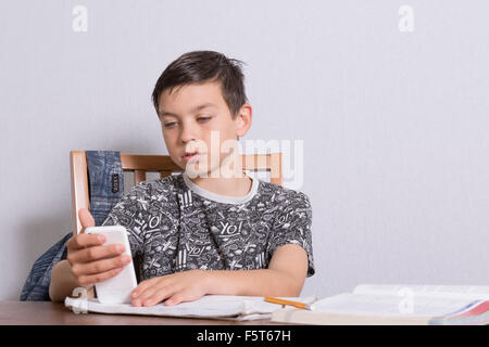 Pre-teen boy distracted by his phone from doing his homework - Stock Photo