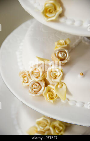 Wedding cake decorated with yellow flower rose buds - Stock Photo