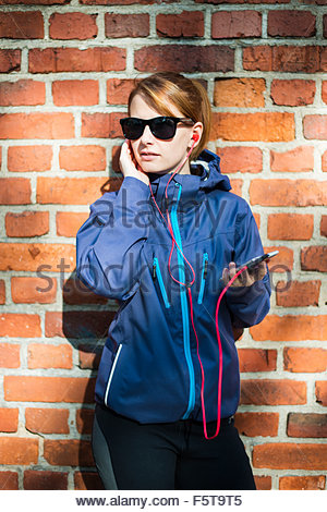 Finland, Uusimaa, Woman standing against wall - Stock Photo