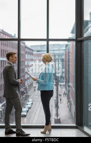 Finland, Helsinki, Business people discussing project by window - Stock Photo