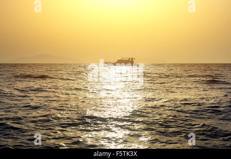 Boat in red sea at the sunset - Stock Photo